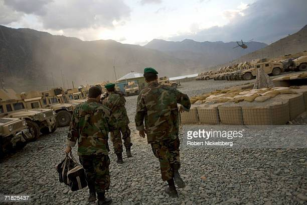 Afghan National Army soldiers walk through the motor pool as a US Army helicopter departs from the Forward Operation Base in September 1 in Naray...