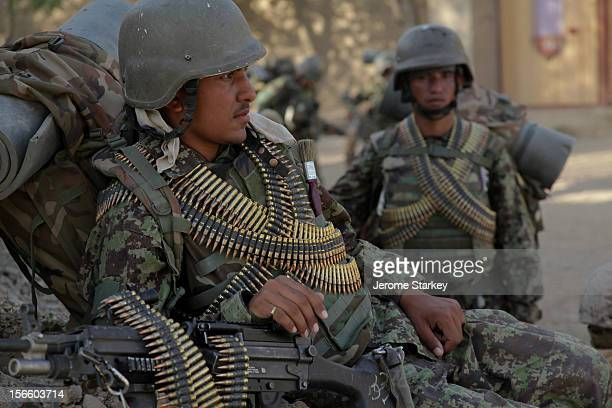 Afghan National Army soldiers wrapped in ammunition belts for their machine guns rest during a foot patrol north of Gereshk in Helmand province in...