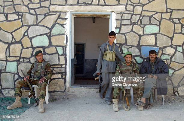 Afghan National Police, blue uniforms, and Afghan National Army soldiers guard the entrance to the district meeting building at the eastern village...