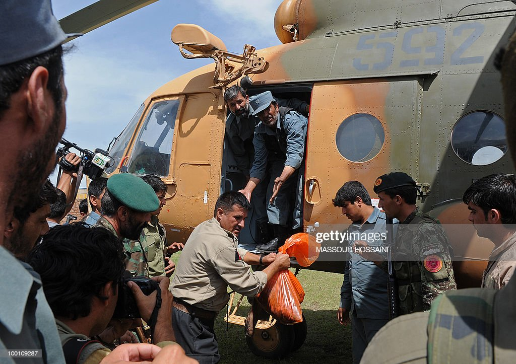 Afghan National Police (ANP) personnel transport a dead body from an Afghan military helicopter in Charikar city of Parwan province, north of capital Kabul on May 21, 2010. Bodies and wreckage of an Afghan passenger plane that crashed with 43 people on board have been found on a mountainside with no immediate sign of any survivors, a government minister said. The ageing Pamir Airways plane was carrying three Britons, an American and dozens of Afghans when it came down during bad weather on May 17 during a scheduled flight from the northern province of Kunduz to Kabul. AFP PHOTO/Massoud HOSSAINI