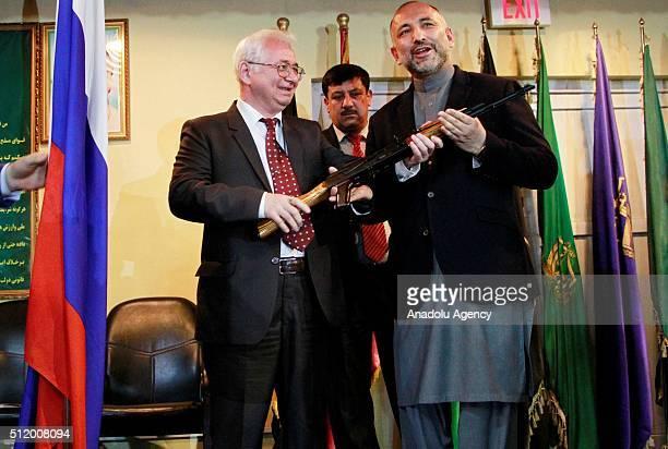 Afghan National Security Adviser Hanif Atmar and Russian Ambassador of Afghanistan Alexander Mantytskiy inspect AK47 during handover ceremony at...