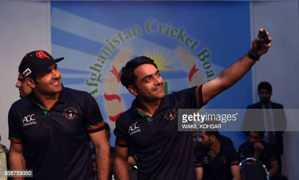 Afghan national team cricketers Rashid Khan and Mohammed Nabi take a 'selfie' during an event to celebrate the Afghan national team qualification to...