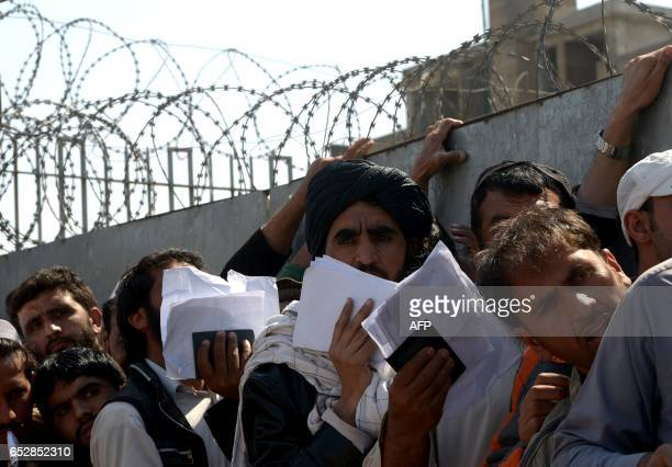 Afghan nationals carry their passports as they wait to extend their visas outside the Pakistani immigration office in Peshawar on March 13 following...