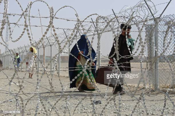 Afghan nationals walk along a fenced corridor after crossing into Pakistan through the Pakistan-Afghanistan border crossing point in Chaman on August...