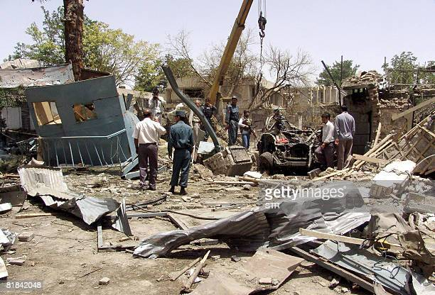 Afghan officials walk at the site of a suicide attack in front of The Indian Embassy in Kabul on July 7 2008 A suicide bomber rammed an...