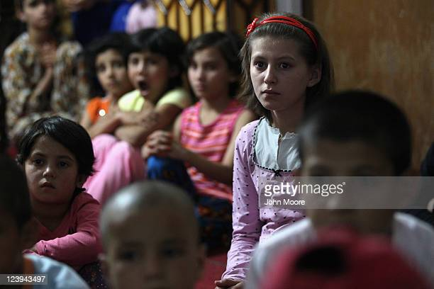 Afghan orphans watch cartoons at the Satara Orphanage on September 6 2011 in Kabul Afghanistan The orphanage is run by the Afghan Child Education and...