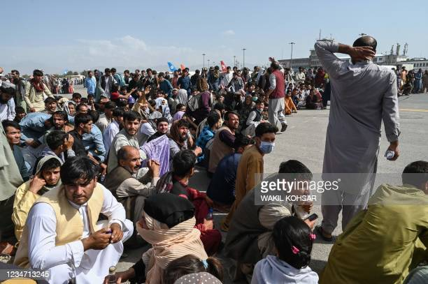 Afghan passengers sit as they wait to leave the Kabul airport in Kabul on August 16 after a stunningly swift end to Afghanistan's 20-year war, as...