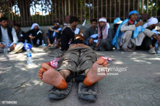 Afghan peace activists rest during a march to demand an end to the war from Helmand as they arrive in Kabul on June 18 2018 Dozens of peace...