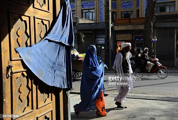 Afghan pedestrians walk at a market in Herat October 19 2014 Afghanistan's economy has improved significantly since the fall of the Taliban regime in...