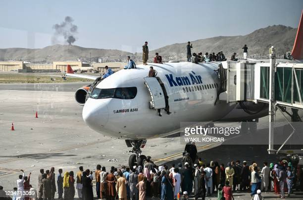 Afghan people climb atop a plane as they wait at the Kabul airport in Kabul on August 16 after a stunningly swift end to Afghanistan's 20-year war,...