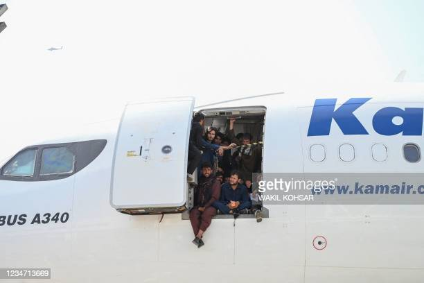 Afghan people climb up on a plane and sit by the door as they wait at the Kabul airport in Kabul on August 16 after a stunningly swift end to...
