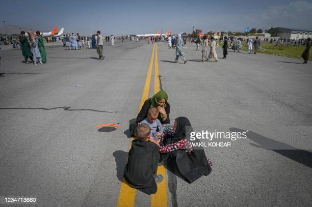 Afghan people sit along the tarmac as they wait to leave the Kabul airport in Kabul on August 16 after a stunningly swift end to Afghanistan's...