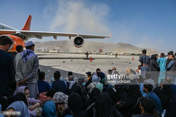 Afghan people sit as they wait to leave the Kabul airport in Kabul on August 16 after a stunningly swift end to Afghanistan's 20-year war, as...