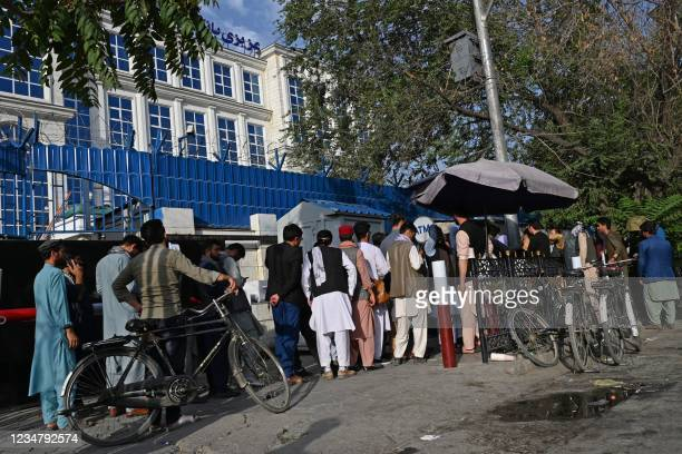 Afghan people stand in a queue as they wait for their turn to collect money from an ATM in front of a bank along a roadside in Kabul on August 21...