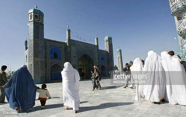 Afghan people walk in front of the of the shrine of HazratiAli also called the Blue Mosque in MazariSharif the capital of Balkh province north of...