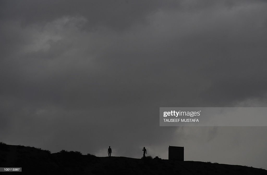 Afghan people walk on the top of a hill as rain clouds approach on nightfall in Kabul on May 21,2010. A soldier with NATO's International Security Assistance Force (ISAF) was killed by a home-made bomb in southern Afghanistan, NATO said. 'An ISAF service member died following an IED strike in southern Afghanistan today,' the alliance said in a statement, referring to an improvised explosive device, the Taliban insurgency's weapon of choice. AFP PHOTO/Tauseef MUSTAFA