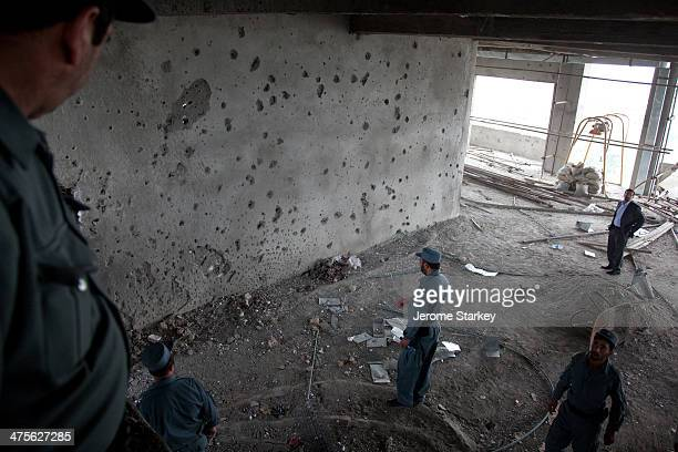 Afghan police and intelligence officials inspect the aftermath of a 20-hour gun battle between insurgents and security forces, September 14, 2011....