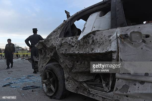 Afghan police and security personnel inspect the scene of a suicide attack near a district police headquarters in Kabul on March 25 2015 A suicide...