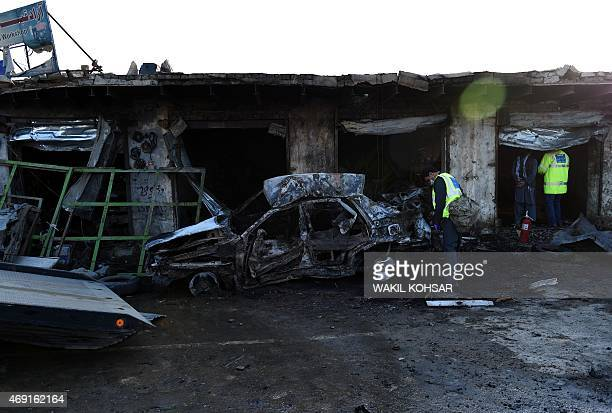 Afghan police and security personnel inspect the scene of a suicide car bomb attack at Dispachari in Kabul on April 10 2015 A suicide bomb attack on...