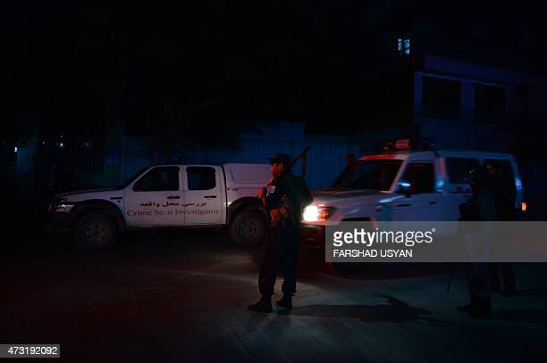 Afghan police officers stand gaurd as ambulances arrive near the Park Place guesthouse in Kabul early on May 14 2015 Gunmen stormed a Kabul...