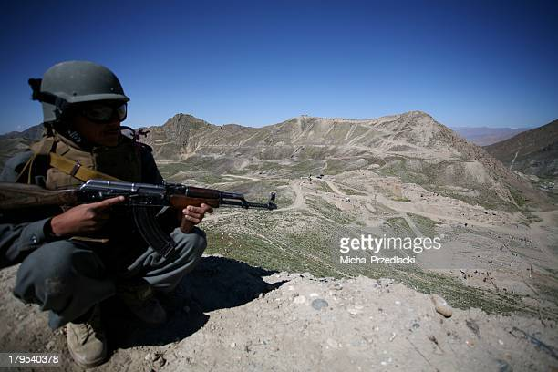 CONTENT] Afghan policeman on guard looking at what is believed to had been the administrative center of the Mes Aynak city Afghan National Police...