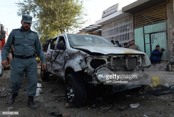 Afghan policeman walks past at the site of a suicide bomb attack near a Shiite mosque in Kabul on September 29 2017 Up to six people were killed when...