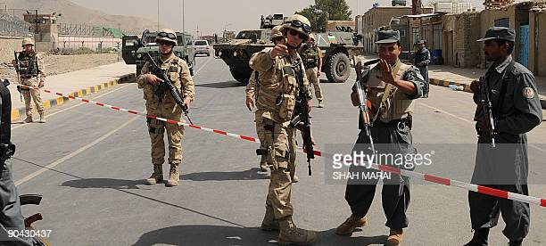 Afghan policemen and a Belgian soldiers of the NATOled International Security Assistance Force block a road at the site of a suicide bomb attack at...