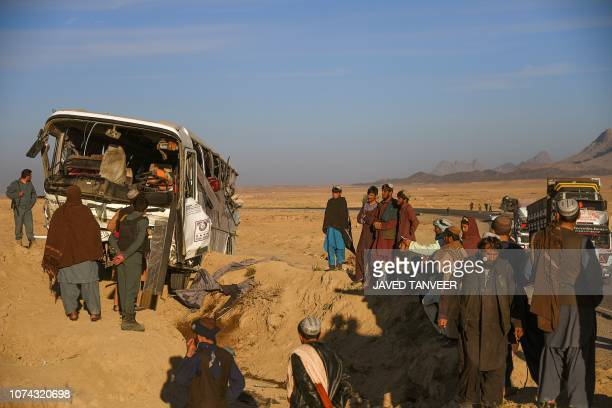 Afghan policemen and bystanders inspect a site after a bus accident collided with a trailer at Daman district on KabulKandahar highway in Kandahar...