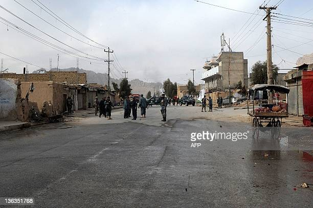 Afghan policemen and US soldiers stand guard at the scene of a suicide attack in Kandahar on January 3 2012 A suicide bomber on a motorbike struck a...