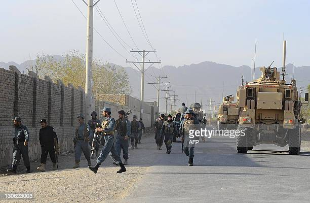 Afghan policemen arrive at the site during gunfire near a US base in Kandahar on October 27 2011 Taliban armed with guns and explosives struck a...