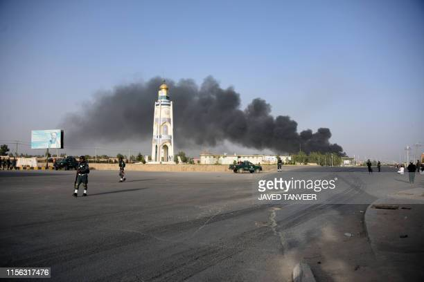 Afghan policemen arrive near a site of a car bomb attack as smoke rises from the Police headquarters in Kandahar province on July 18 2019