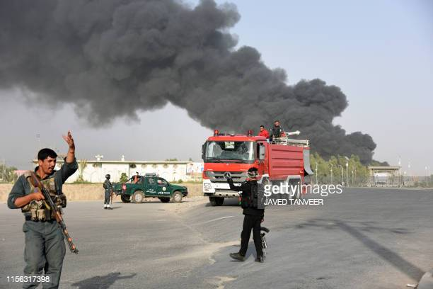 Afghan policemen arrive near a site of car bomb attack as smoke rises from the Police headquarters in Kandahar province on July 18 2019