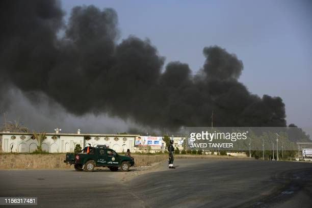 TOPSHOT Afghan policemen arrives near a site of car bomb attack as smoke rises from the Police headquarters in Kandahar province on July 18 2019