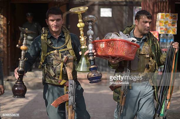 Afghan policemen carry shisha pipes during a raid confiscating shisha water pipes in Kabul on November 30 2016 In a crack down on cafes and...