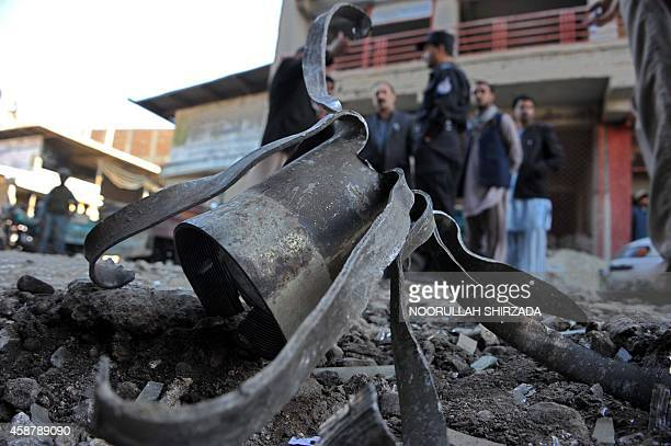 Afghan policemen inspect the site of a rocket attack in Jalalabad the capital of Nangarhar province on November 11 2014 Three rockets allegedly fired...