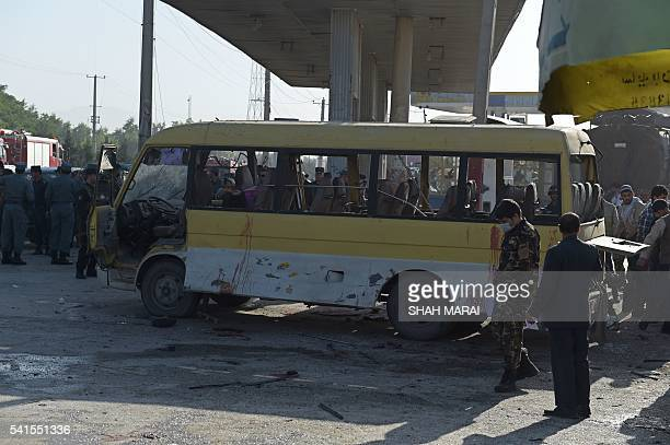 TOPSHOT Afghan policemen look at the site of a suicide attack to have hit a minibus carrying foreign security guards in Kabul on June 20 2016 A...