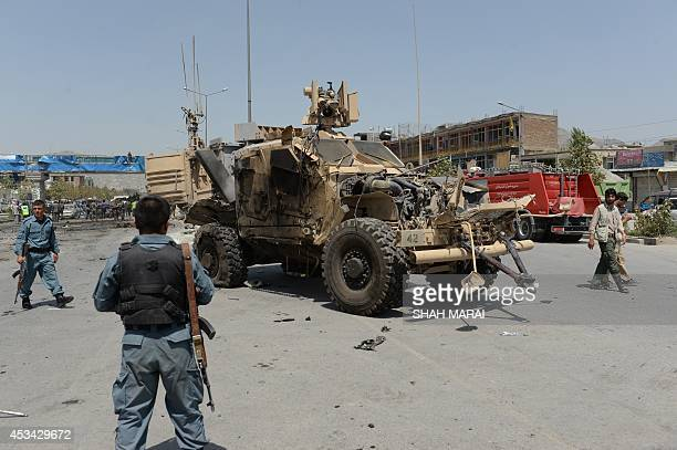 Afghan policemen look at the wreckage of an armoured vehicle of NATOled International Security Assistance force at the site of a suicide attack in...