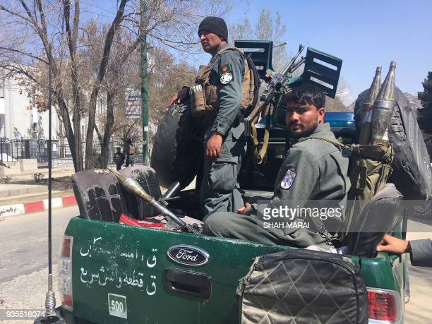 Afghan policemen look on near the site of a suicide bombing attack in Kabul on March 21 2018 A suicide bomber blew himself up in front of Kabul...