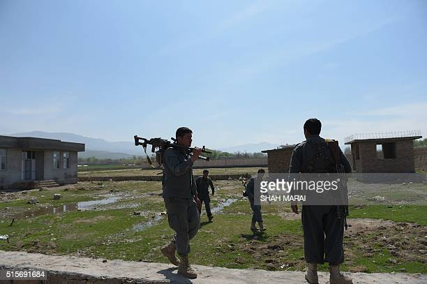 Afghan policemen patrol in DandeGhori district in Baghlan province on March 15 following weeks of heavy battles to recapture the area from Taliban...