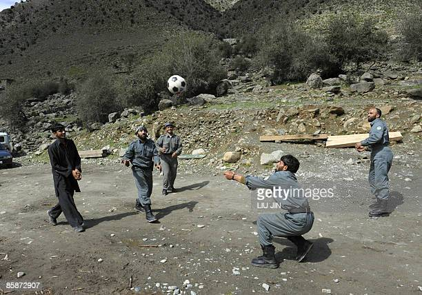 Afghan policemen play a ball game at a police station in Naray town, in Afghanistan's eastern Kunar province on April 9, 2009. US President Barack...