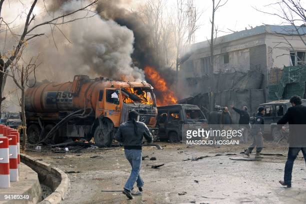 Afghan policemen run at the site of a suicide attack in front of the German embassy in Kabul on January 17 2009 A suicide bomb exploded near the...