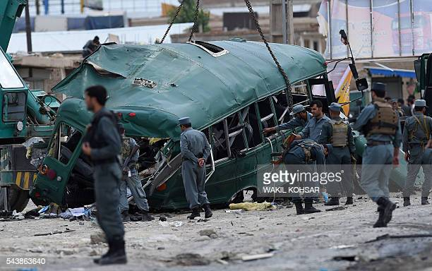 Afghan policemen search the wreckage of a bus at the site of a suicide bomb attack that targeted a convoy of buses transporting police cadets on the...
