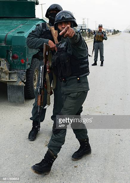 Afghan policemen set up a perimeter in the vicinity of the Afghan election commission during an attack on the election centre in Kabul on March 29...