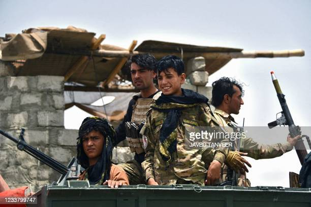 Afghan policemen sit on an armored vehicle at a checkpoint in Panjwai district of Kandahar province on July 4 after the Taliban captured a key...