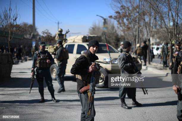 Afghan policemen stand guard after explosions at a Shiite cultural centre in Kabul on December 28 2017 Around 40 people were killed and dozens more...