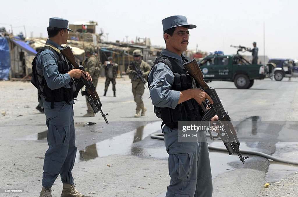 Afghan policemen stand guard as two US s : News Photo