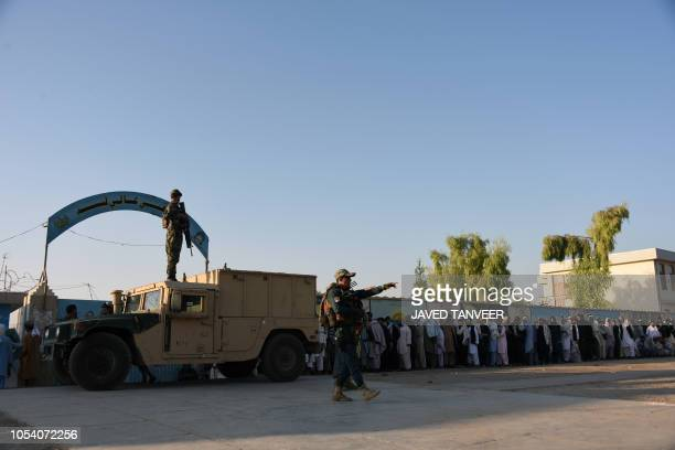 Afghan policemen stand guard as voters wait to cast their votes at a polling centre for the country's legislative election in Kandahar on October 27...
