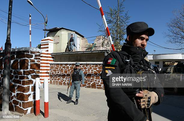 Afghan policemen stand guard at the entrance to police headquarters in Kabul on November 9 2014 A suicide bomber has walked into the offices of the...