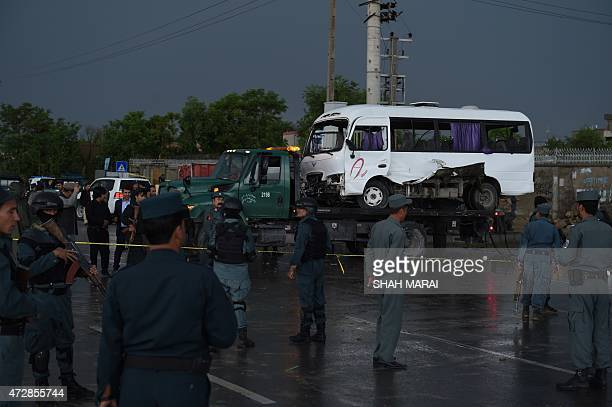 Afghan policemen stand guard at the scene of a suicide bomb attack in Kabul on May 10 2015 A Taliban suicide bomber struck a government bus in Kabul...
