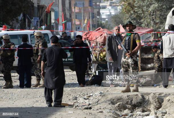 TOPSHOT Afghan policemen stand guard at the site of a suicide bomb attack near a Shiite mosque in Kabul on September 29 2017 A suicide bomber posing...
